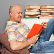 Senior man reading the book at home - Stock Photo