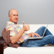 Royalty-Free Stock Photo: Man with laptop at home showing thumbs up