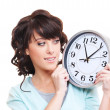 Studio shot of smiley woman looking at clock — Stock Photo