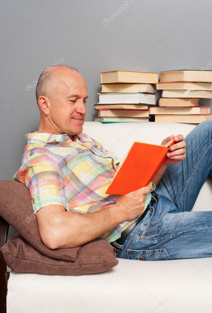 Smiley senior man reading the book at home — Stock Photo #10222005