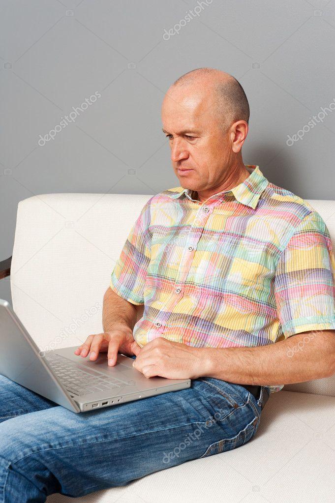 senior homme en jeans assis avec ordinateur portable la maison photographie konstantynov. Black Bedroom Furniture Sets. Home Design Ideas