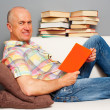 Smiley elderly man reading interesting book - Stockfoto