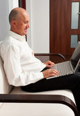 Man in shirt with laptop at home — Stock Photo