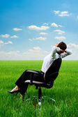 Woman relaxing in armchair at the meadow — Stockfoto