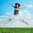 Happy woman jumping at the field — Stock Photo