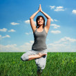 Woman practicing yoga at the field — Stockfoto