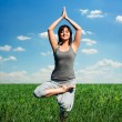 Woman practicing yoga at the field — Stock Photo