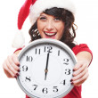 Excited girl with santa hat holding clock — Stock Photo