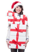 Woman in santa hat holding gift boxes — Stock Photo