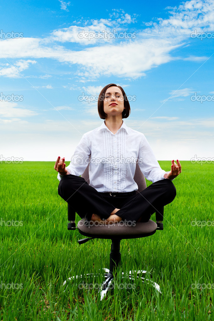 Businesswoman sitting in lotus position on armchair in green field — Stock Photo #8130066