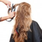 Hairdresser straightening hair — Stock Photo