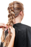 Hairdresser doing up one's hair in a plait — Stock Photo