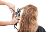 Hairdresser straightening hair — Stock Photo