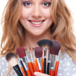 Smiley woman with make-up tools - Stock Photo