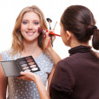 Professional make-up artist working with model — Stock Photo