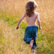 A child running along a path in the field — Stock Photo