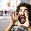 Portrait of young man screaming at a crowded city - Stock Photo