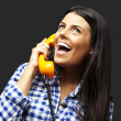 Portrait of young woman talking on vintage telephone over black — Lizenzfreies Foto