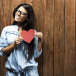 Stock Photo: Portrait of young woman holding heart symbol against a wooden wall