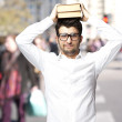 Portrait of young student holding books on his head at street — Stock Photo