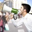 Portrait of young man screaming with megaphone at city — Stock Photo #10178117