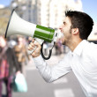 Portrait of young man screaming with megaphone at city — Stock Photo