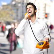 Portrait of young man talking on a vintage telephone at street — Stock Photo #10178351