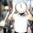 Portrait of man holding a big clock in front of hid head at a cr — Stock Photo #10178429