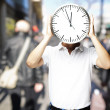 Stock Photo: Portrait of mholding big clock in front of hid head at cr
