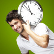 Portrait of a handsome young man carrying a clock against a gree — Stock Photo #10178431