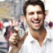 Portrait of young man laughing and showing a stopwatch at a crow — Stock Photo #10178480