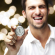 Portrait of young man laughing and showing a stopwatch against a — Photo