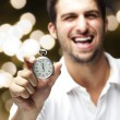 Portrait of young man laughing and showing a stopwatch against a — Stockfoto