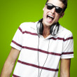 Stock Photo: Portrait of handsome young mlistening to music over green b
