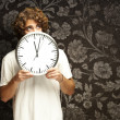 Man hidden behind clock - Stock Photo
