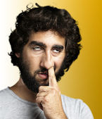 Young man with the finger in his nose over yellow background — Stock Photo