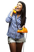 Portrait of young woman talking on vintage telephone over white — Stock Photo