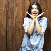 Portrait of young woman surprised against a wooden wall — Stock Photo