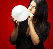 Woman blowing balloon — Stock fotografie