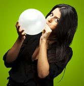 Woman blowing balloon — Stock Photo