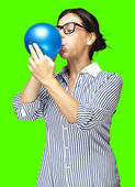 Woman blowing a balloon — Stock Photo