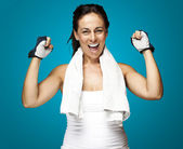 Portrait of a middle aged woman gesturing win symbol over blue — Stock Photo
