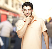 Portrait of a comely young man thinking at a crowded street — Stock Photo