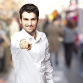Portrait of a handsome young man pointing with finger at a crowd — Stock Photo