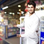 Ritratto di un giovane bello, invitando ad per entrare al negozio — Foto Stock