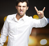 Portrait of young man doing rock symbol at city by night — Stockfoto