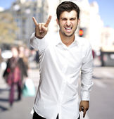 Portrait of young man doing rock symbol at city — Photo
