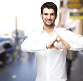 Portrait of young man doing heart symbol at street — Stock Photo