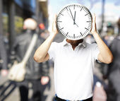 Portrait of man holding a big clock in front of hid head at a cr — Stock Photo