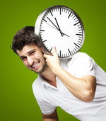 Portrait of a handsome young man carrying a clock against a gree — Stock Photo